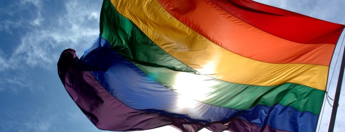 Rainbow_flag_and_blue_skies-1038x400